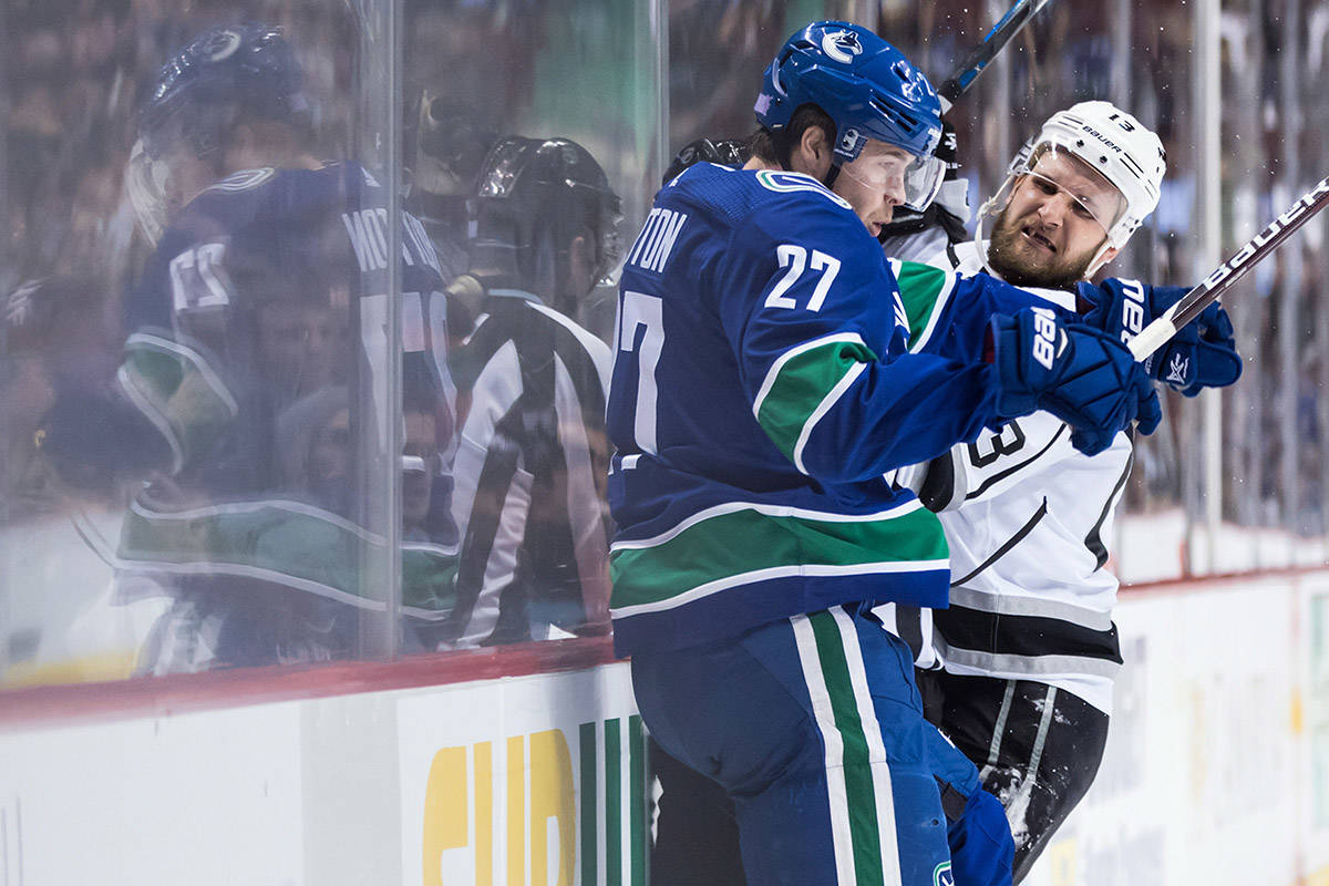 Vancouver Canucks' Ben Hutton (27) and Los Angeles Kings' Kyle Clifford (13) collide during the first period of an NHL hockey game in Vancouver, on Tuesday November 27, 2018. THE CANADIAN PRESS/Darryl Dyck